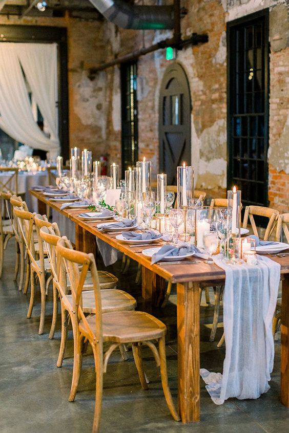 an industrial reception space with brick walls, wooden tables and chairs, blue and neutral linens plus candles