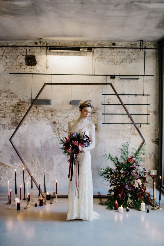 an industrial space with a hex arch, tall jewel tone candles and a bold floral arrangement