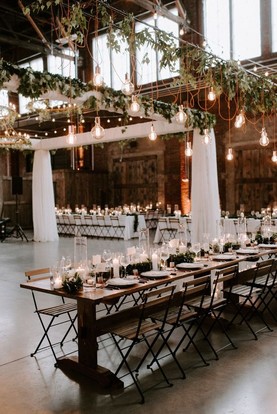 an industrial space with brick walls, hanging bulbs, greenery and candles on the tables is welcoming