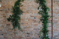 an industrial wedding ceremony space with a greenery wedding arch and pillar candles on the floor
