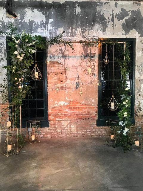 an industrial wedding ceremony space with a metal arch decorated with greenery, white blooms and candle lanterns