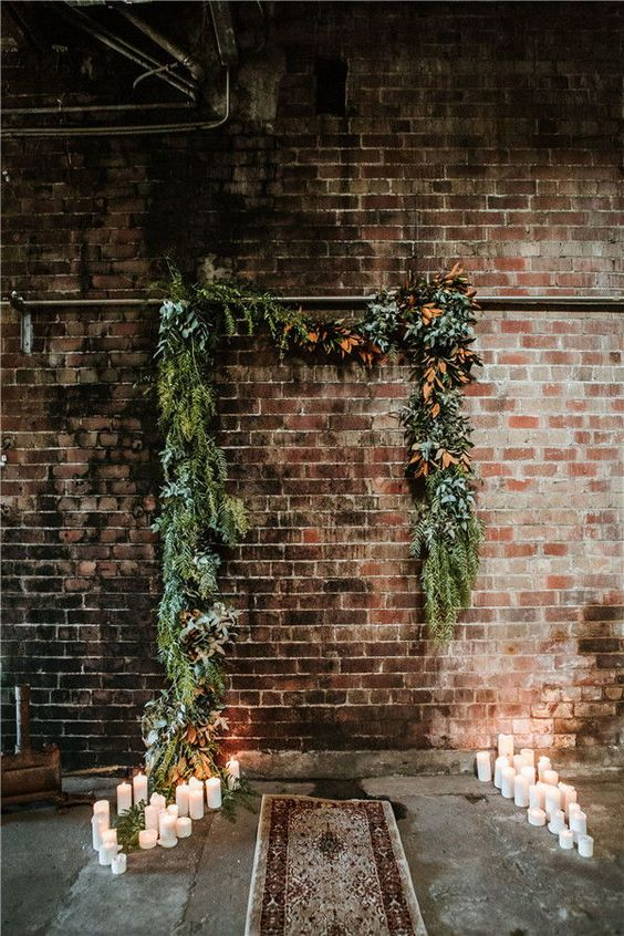 an industrial wedding ceremony space with greenery and dried foliage, pillar candles and a boho rug looks chic