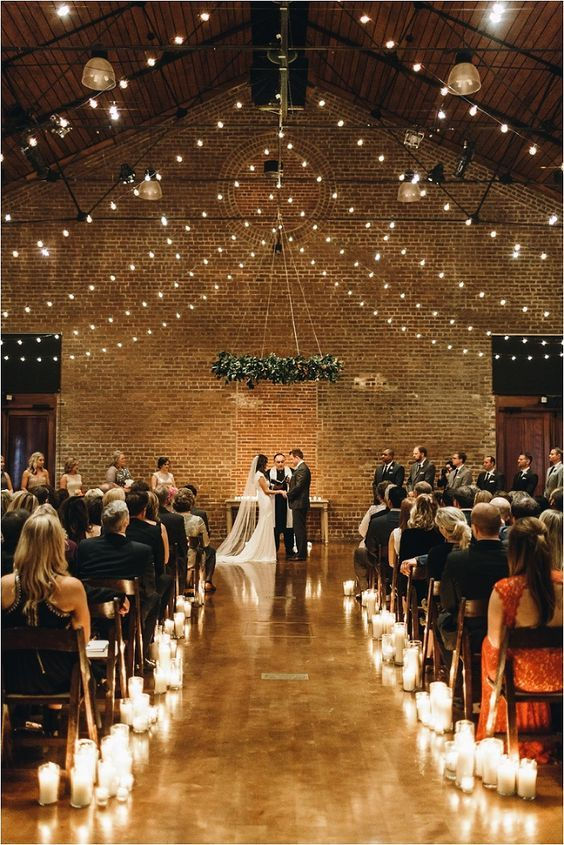 an industrial wedding ceremony space with lights over the space, candles to line up the aisle and a greenery chandelier