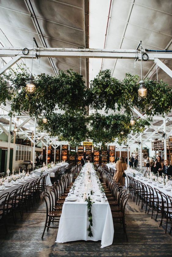 an industrial wedding reception space with a metal roof, hanging greenery and lamps and white linens