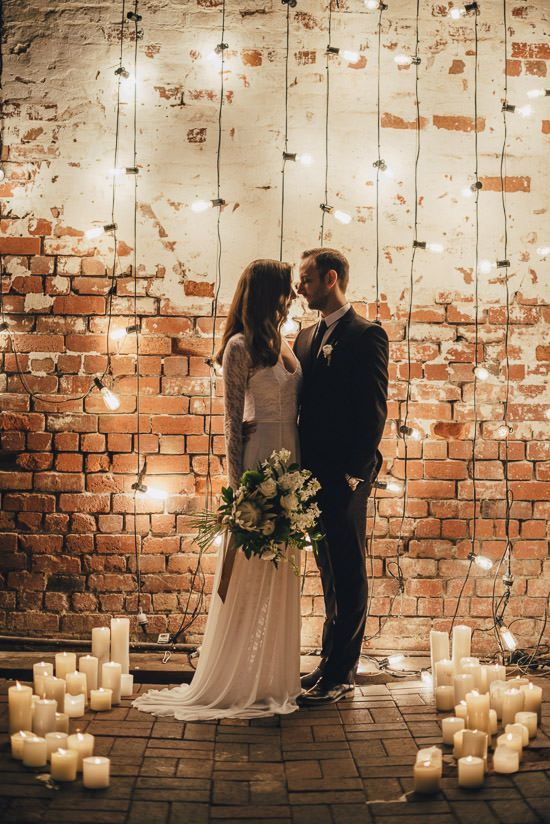 an industrial wedding space decorated with lights and pillar candles that create a small altar