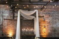 an industrial wedding space decorated with white curtains, candles in glass candleholders, candles to line up the aisle, greenery on the chairs