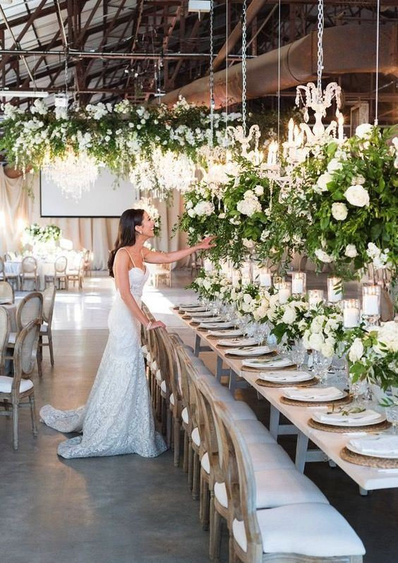 an industrial wedding space with a metal and glass roof, exposed pipes and hanging chandeliers decorated with greenery and white blooms