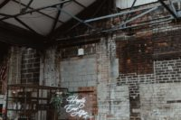 an industrial wedding space with shabby bricks, a metal arch with greenery and a neon sign, candles and floral arrangements