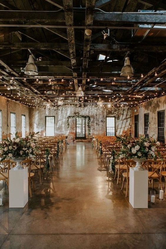 an industrial wedding venue decorated with lights, with lush floral and greenery arrangements and greenery on chairs
