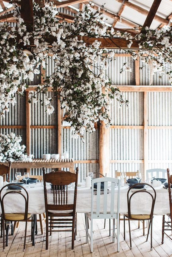an industrial wedding venue done with corrugated steel, wooden beams, oversized cotton branch chandeliers