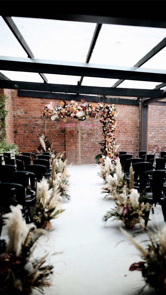 an industrial wedding venue with brick walls, metal beams, a glass roof, metal chairs and pampas grass