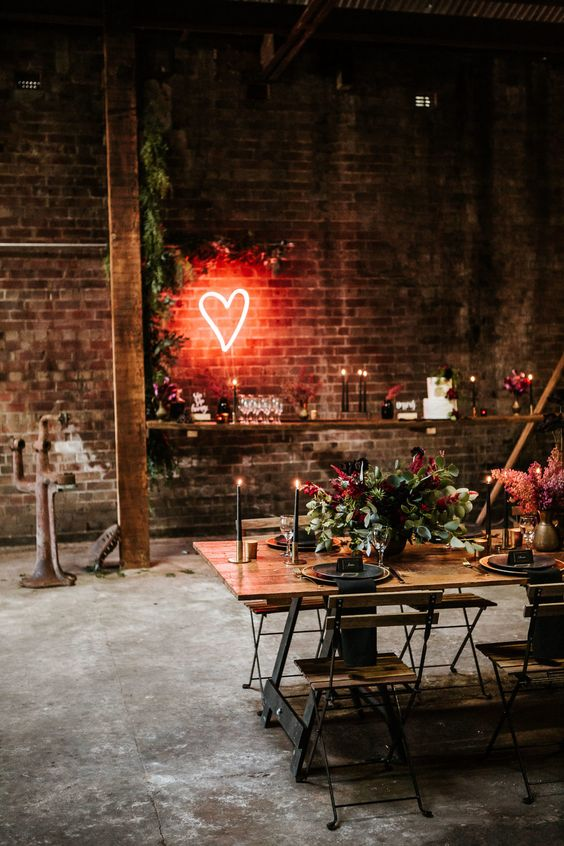 an industrial wedding venue with brick walls, tables and chairs, wooden beams softened with greenery, bright blooms and neon