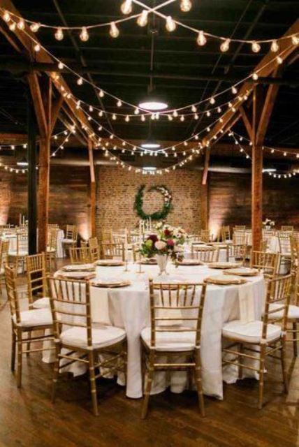 an industrial wedding venue with brick walls, wooden pillars and lights hanging and refined tablescapes with bright blooms