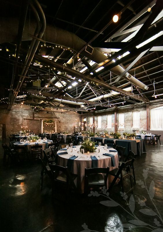 an industrial wedding venue with exposed pipes and metal, brick walls and elegant blush and navy tables