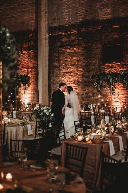 an industrial wedding venue with red brick walls, concrete beams, tall greenery centerpieces and candles all over the space