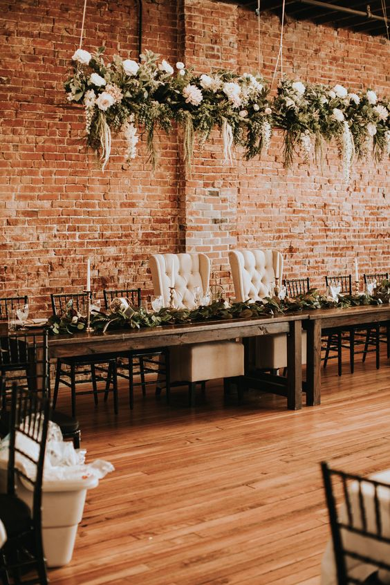 an industrial wedding venue with red brick walls, wooden tables and chic chairs, white blooms and greenery hangings