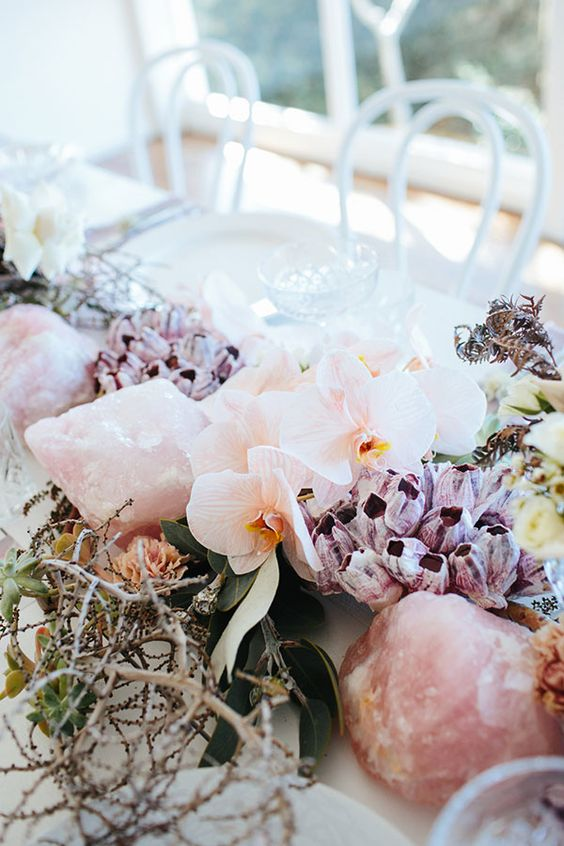 beautiful reception table decor with purple and blush blooms, rose quartz, twigs and branches