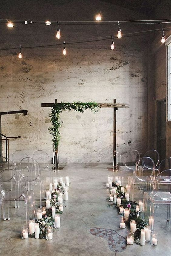 candles and greenery to line up the aisle with ghost chairs and a wedding arch decorated with greenery