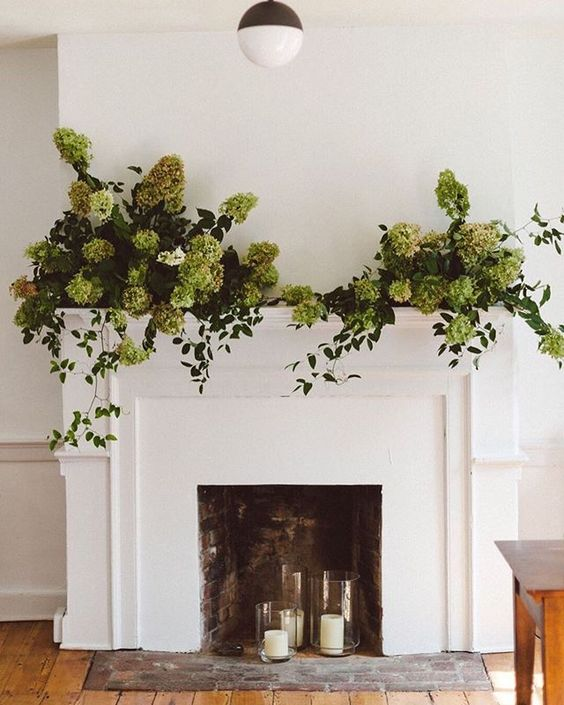 candles in glass candleholders, greenery and green hydrangeas make the fireplace stand out contrasting to the greens