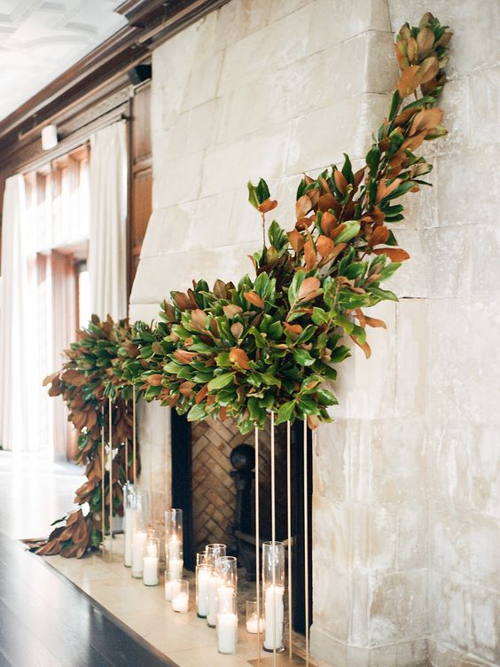 candles in tall glasses and a lush magnolia leaf garland going from above to the floor make the fireplace adorable