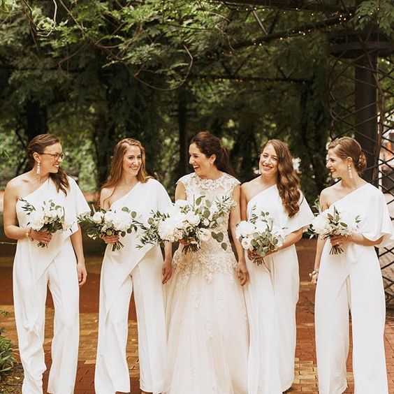 chic one shoulder bridesmaid jumpsuits with draped bodices and wideleg pants plus statement earrings for a modern wedding