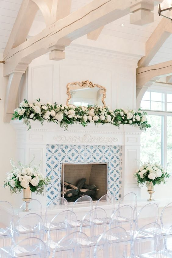 elegant fireplace decor with lush white blooms and greenery is a cool idea to accent the fireplace