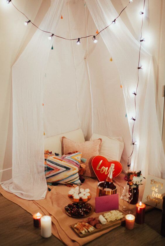 even if there's a lockdown, you may organize a tiny engagement picnic at home, add lights, pillows and blooms