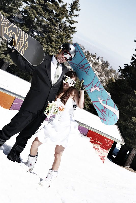 fun wedding portraits of the couple showing off their snowboards right in the snow on the mountains