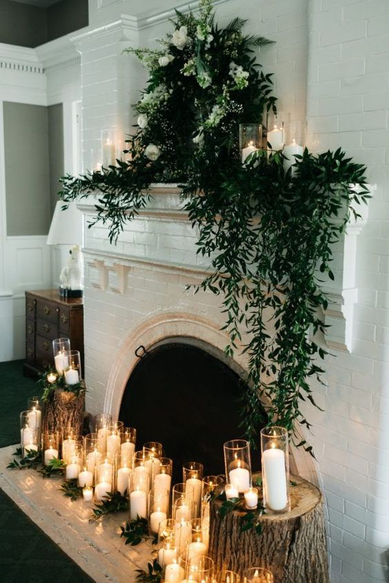 greenery decor, a greenery and white flower wreath, candles in glasses for a woodland touch to the fireplace