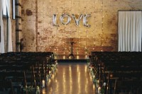 an industrial wedding ceremony space with shabby brick walls, lights, candles lining up the aisle and shiny metallic LOVE letters