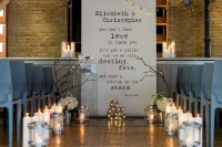 an industrial wedding ceremony space with a letter backddrop, candle lanterns, candles, branches and metal chairs for a cool look