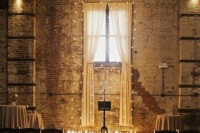 a dark industrial wedding space with shabby brick walls, lights and curtains, candles to decorate the altar and line up the aisle