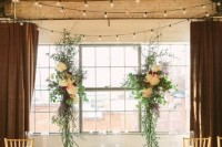 an industrial wedding ceremony space with a wooden ceiling with metal beams, lights and a lush floral altar to soften the space