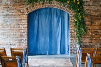 an industrial wedding space with brick walls, wooden chairs, greenery and bright bloom decor, bright blue curtains and ribbons on the chairs