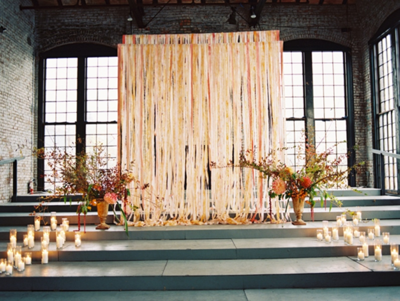 a wedding ceremony space with colorful fabric ribbons, bright blooms in vases and candles to line up the altar