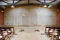 an industrial wedding ceremony space with candles, dried branches and a wire backdrop decorated with white blooms plus lamps over the space
