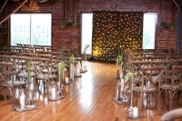an industrial wedding ceremony space with brick walls, greenery, a greenery wall with blooms, candles and greenery attached to the chairs