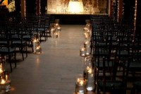 a dark industrial space with lights, candles to line up the aisle and lots of candles on the scene looks cool