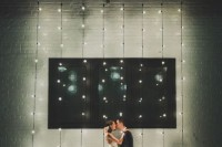 a wedding ceremony space with white brick walls, lights, dried bloom arrangements for a simple and stylish modern look