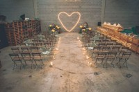an industrial wedding ceremony space with pallets, metal and wood chairs, candles and a neon heart instead of a wedding arch