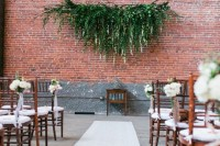 an industrial wedding cermeony space with a lush greenery decoration and white blooms and ribbon bows to soften the space