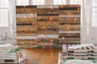 a wedding ceremony space with a reclaimed wooden backdrop decorated with lights and pallet benches decorated with candles and pillows