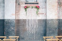 a rough industrial wedding space with a cool macrame and bright blooms and greenery backdrop plus wooden chairs