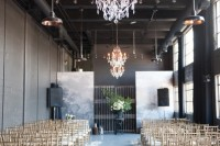 a dark wedding space spruced up with crystal chandeliers, watercolor backdrops, petals on the floor and candles to line up the aisle