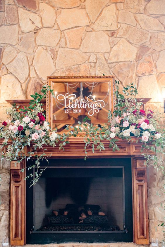 lush floral decor and greenery and a mirror in a frame make the fireplace very stylish and very chic