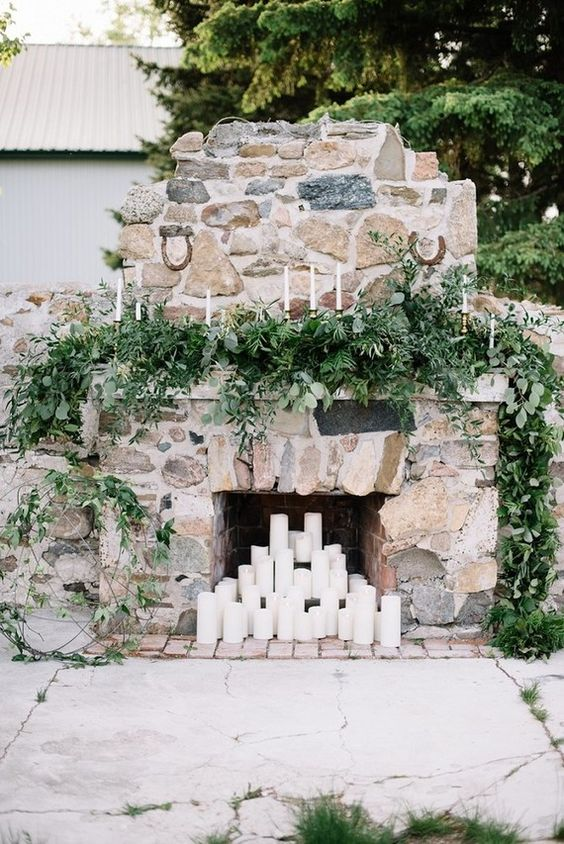 lush textural greenery and pillar candles in the fireplace make it look very fresh and veyr natural