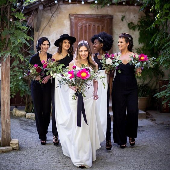 mismatching black jumpsuits and lacey black heels for all the bridesmaids to contrast the white bridal look