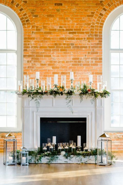 modern and delicate fireplace styling with floating candles and those in elegant candleholders, greenery and bright blooms