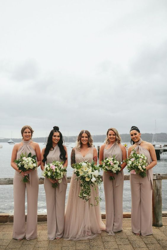 off-white bridesmaid jumpsuits with various necklines and wideleg pants is a comfy modern idea for your bridal party