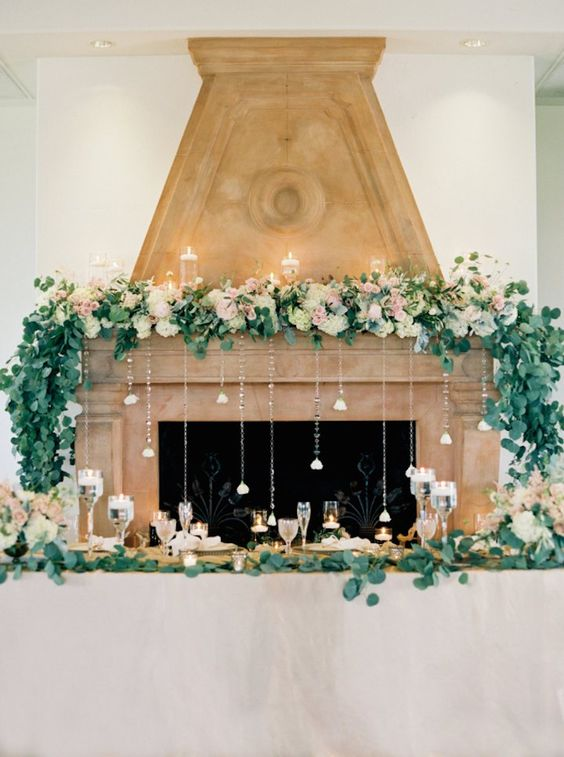 pastel blooms, greenery, floating candles and crystals hanging down from the mantel for a delicate and chic look